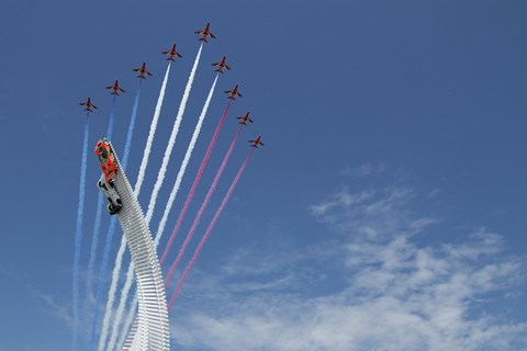 The Red Arrows fly past the Goodwood sculpture. Note the sun!