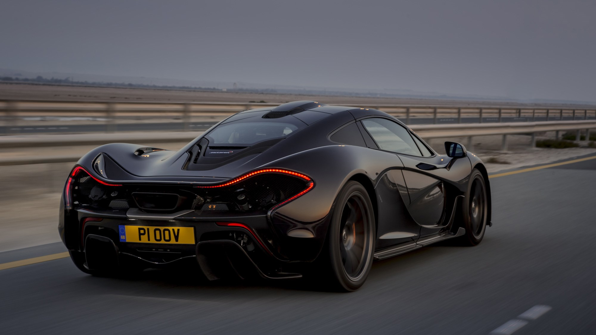 McLaren P1 review, Bahrain, black, rear view, driving on the road
