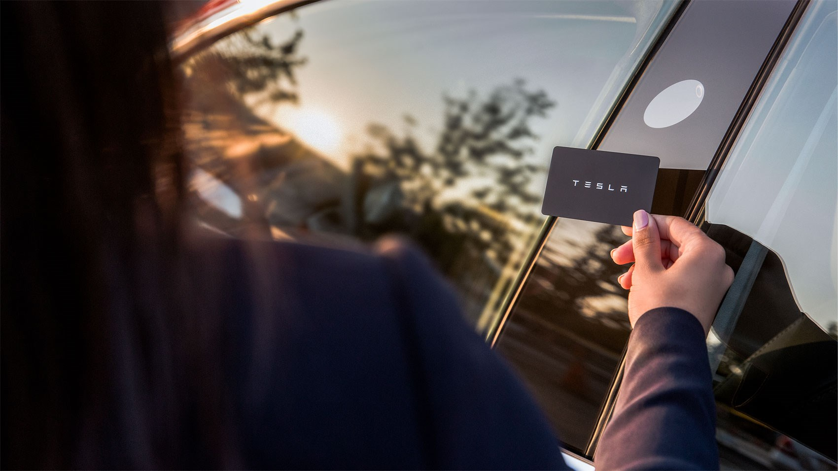 Hold up a Tesla credit card size access key to the B-pillar to unlock the Model 3