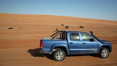 VW Amarok driving in the desert, passing a camel