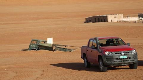 VW Amarok and old buried truck at 1000 Nights desert camp in Oman