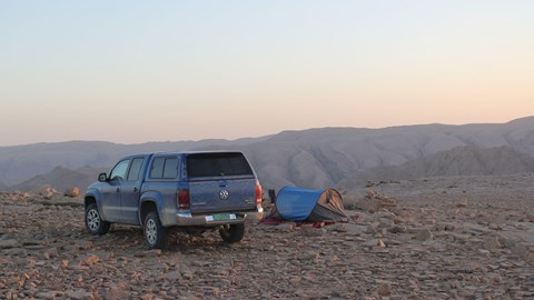 VW Amarok next to tent on rock in Oman