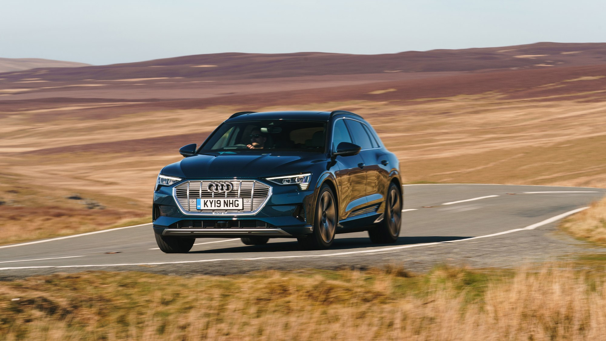 Here it is, the most important Audi in decades; the all-electric e-Tron SUV. The first step of a ascendance from nitrogen dioxide sinner to aspiring zero-emission saint, the handsome-looking EV is just the beginning for Ingolstadt's electric plans. After this, there'll be a flurry of EVs from the four rings, with a Sportback and a J1-based e-Tron GT Coupe following soon after.   Available to order now with the first UK deliveries only just rolling out of the factory, the new 2019 Audi e-Tron has a certified 241-mile electric range, and promises trademark Audi performance, four-wheel drive, the usual quality interior – and cleaner guts.   We were there when the e-Tron was first revealed in San Francisco, and we've driven it on the worldwide launch, too. It can tick all the boxes in Dubai – but can the e-Tron do it on a cold day in North Yorkshire? Keep reading for our full UK review.   ***What's the UK-spec Audi e-Tron like inside?   Slip into the e-Tron, and it fits Audi's tagline for the car perfectly. 'EV goes Audi' is the ethos inside and out, and that means the e-Tron's cabin could be in any Q car.   The touchscreen-heavy cabin invites you to swipe and pinch just like the A8 – and even the steering wheel isn't particularly EV-alike. The cruise control switches are lifted straight from the TTS we've driven here, and there are paddles, too – which we'll get to later.  In fact, it's the only the transmission where the e-Tron dares to be different – and that's because it doesn't have one. Instead, the area between the passenger and driver is full of storage space with cubby holes, cup-holders and a wireless phone charger all packed into a rather bulky, plastic frame. We'd rather the empty space.   Still the e-Tron does differentiate itself with an unusual thumb-flicking drive selector. Mounted under a hand rest, it's pleasingly tactile - and is clicked forward and back by your thumb and index finger. It's a small thing, but it's something you'll notice every time you drive.   ****Well. how does the e-Tron actually drive, then?   Click into Drive, gingerly apply the throttle – this car won't creep forward like a Tesla – and the firmness of the pedal is the first big surprise. The e-Tron is a 2.5-tonne SUV, with a right pedal more McLaren-like than you'd think. It quietly makes you less blunt with your inputs, and in S mode, it gives the car a sportier feel, too. It's a win-win.   Flex the power of the e-Tron with your foot to the floor, and it accelerates in a progressive, but ultimately physics-bending way, and eerie silence is quickly overtaken by wind and road noise.   ****What's it like to drive in the UK?   That instant torque makes entering  roundabouts easier, allowing you to more safely dart into gaps, and it makes overtaking a simple, effortless experience, too. Passing another car is as simple as checking the oncoming traffic, easing on the power and slotting in front. No hesitant kickdowns, no noise –  just a whoosh. Seamless.   As for the ride? Even on North Yorkshire's roughest roads, the e-Tron delivers a composed, and planted ride comfort regardless of the setting you're on. Flick into Comfort using the very familiar Drive Select button, and you'll find the throttle response rounded off, lighter steering and the bumps smoothed out.   Move over to Sport; power response is instant, the wheel weights up and you feel those nooks and crannies in the surface of the tarmac a little more. Body roll, while minimal in Comfort, is further reduced in Sport, and makes you want to push the 2.5-tonne SUV just a bit harder.  Braking uses both discs and energy-saving regen, seamlessly switching between the two depending on your application. It works very well, with little jolting or juddering as the system switches between the two.  On motorways, you'll find the e-Tron like any other car – except for its effortless ability to overtake. Wind noise and tyre noise are even more apparent without the hum of combustion, though, and you'll notice whistling around around the wing mirrors and A-pillars.  We were driving a conventionally mirrored model; it'll be interesting to see if the lower-dragged, electric-cameras have a big impact on wind noise. And some more on the e-Trons webcams. They're actually legal in the UK, and they're able to slightly enhance the image they receive, so you actually see more with them in low-light conditions.    They're standard with the £82,270 Launch edition e-Tron - not the entry-level £71,520 car. If you want them on anything other than launch-spec, the cameras will set you back £1250.   And what about those paddles? Look around the cabin, and you won't find a B-mode for increased regen; instead, Audi's mapped that function to paddles behind the wheel. Tap the + paddle to increase resistance and energy recovery, and pull the – paddle for less. In some ways, it makes sense to have it behind the wheel;  it's a form of engine braking or 'gear' use – but it'll take  time to learn and use it intelligently.   ****Newton still wins  Of course, the new Audi e-Tron isn't a sports car, and when you're doing anything other than accelerating in a straight line , it can't really repeal the laws of physics. Body roll isn't a large factor, but, the height and the weight of the car is more apparent on corner entry. It's very much the same experience you get in something like a Tesla Model X; it's a supercar when going straight ahead, but you're acutely aware of every kg of its weight when you're doing anything else.   ****UK verdict?   In many ways, the e-Tron is just like any other Audi, inside and out - but that's what makes it exciting. It's an SUV you can imagine slotting easily into your everyday life, with more charging options, and packages easing you over the ever-shrinking hurdles of EV ownership.