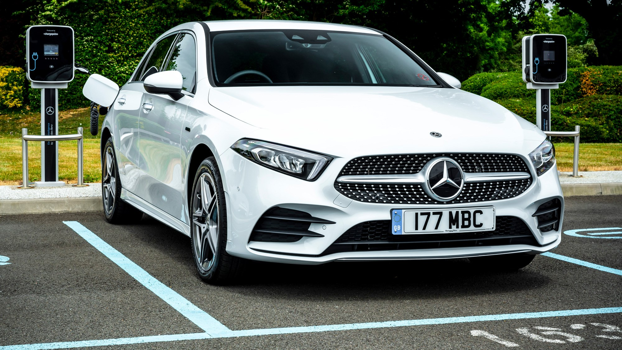 Mercedes-Benz A250e plug-in hybrid review, 2020, white, side view, charging