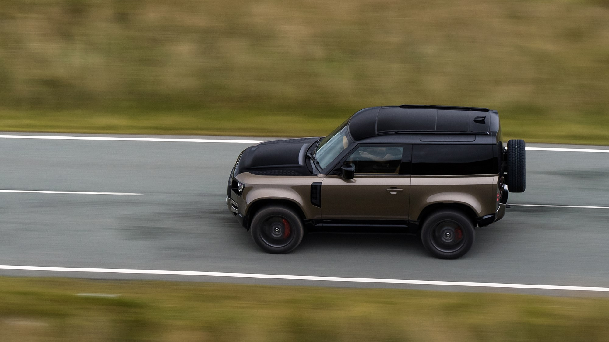 Gold 2021 Land Rover Defender 90 X P400 driving from above