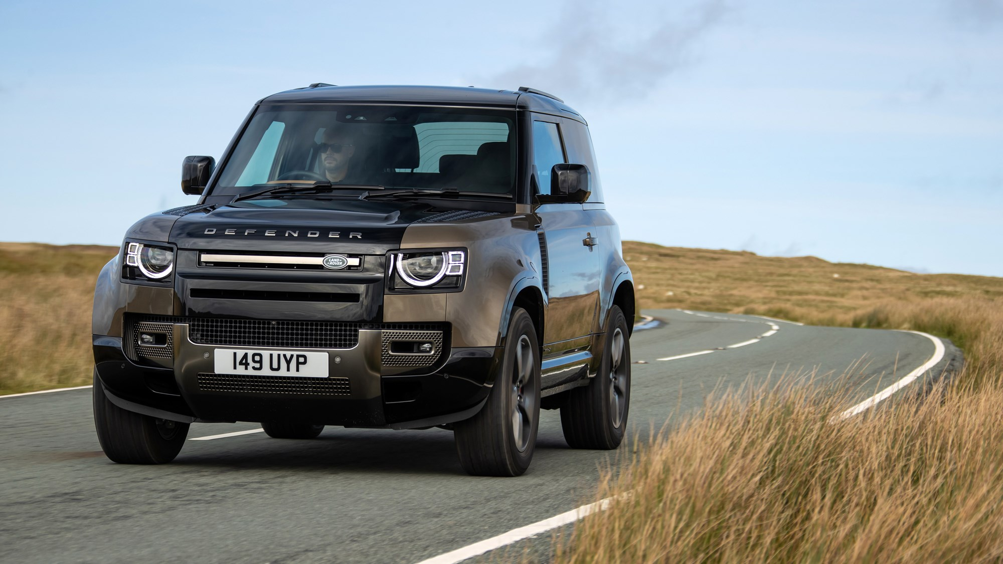 Gold 2021 Land Rover Defender 90 X P400 driving front three-quarter