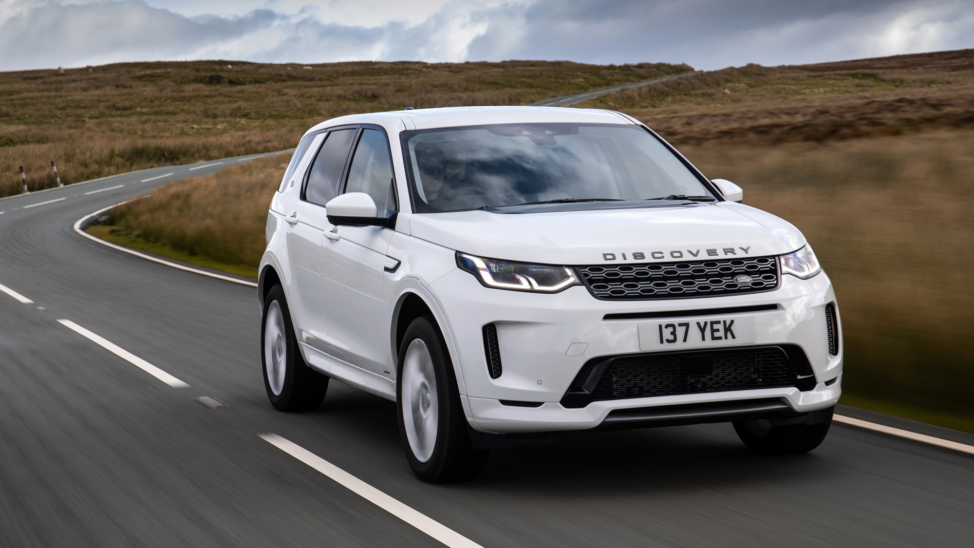 White Land Rover Discovery Sport P300e front three-quarter driving