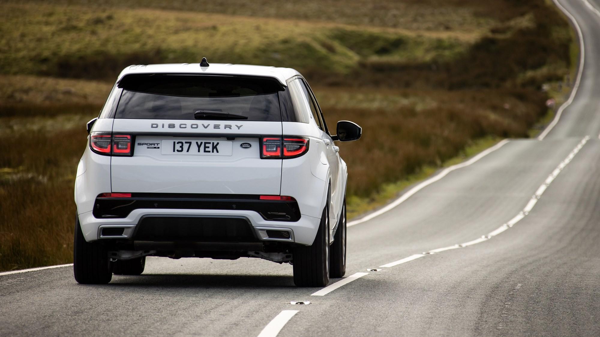 White Land Rover Discovery Sport P300e rear three-quarter driving