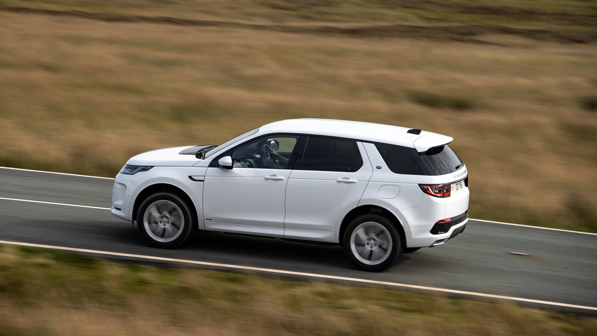White Land Rover Discovery Sport P300e rear three-quarter driving
