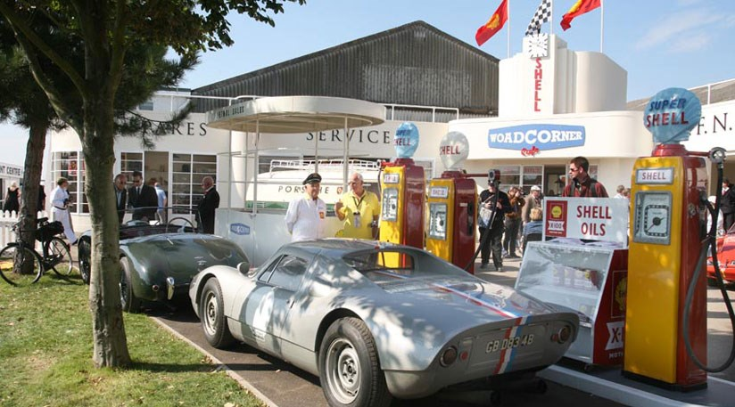 A Porsche 904 pulls up to the pumps in front of the Woad Corner garage display